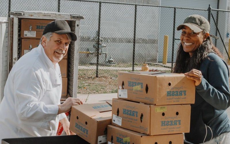 Sharee Dorsett (left), co-pastor of Wilmington's City of Love Church, receives a donation of food from 现金足球网's catering executive chef, Carl Zampini. The vegetables and other items fed around 500 families in two-and-a-half days.