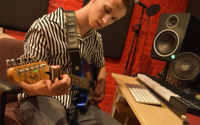 student holds a guitar