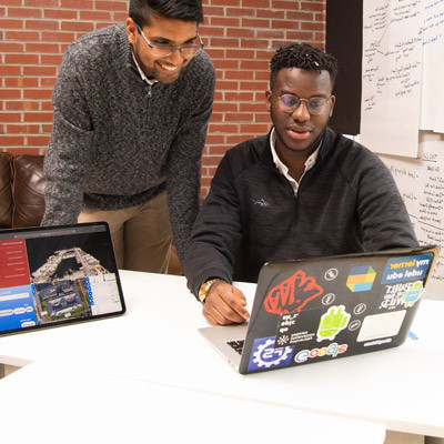 Two students standing over a laptop
