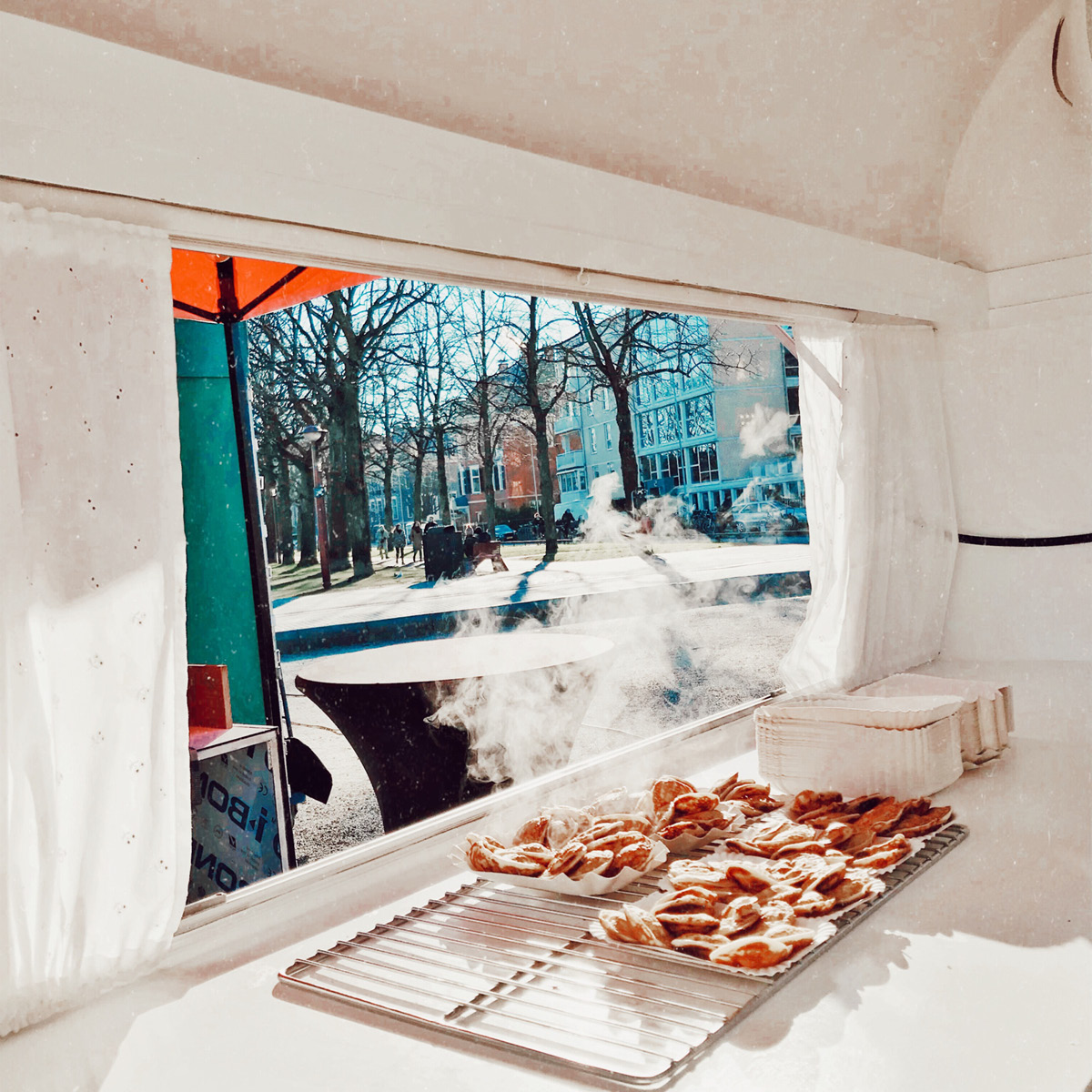 A photo from inside a food truck looking out and Dutch Pancakes sitting  in a pile.