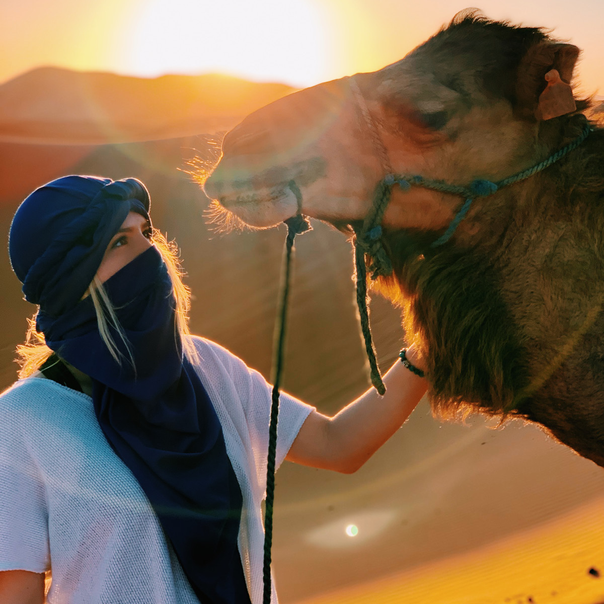 A student looks at a camel and poses for a photo against sun and sand.