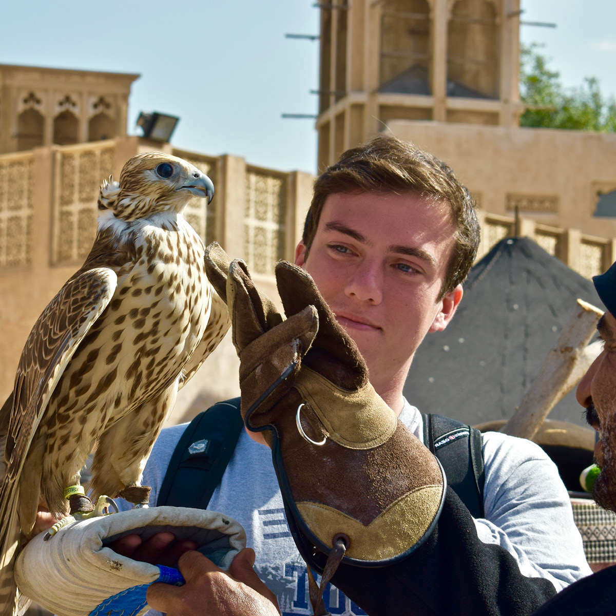 A 现金足球网 student stands alongside a falcon and its trainer.