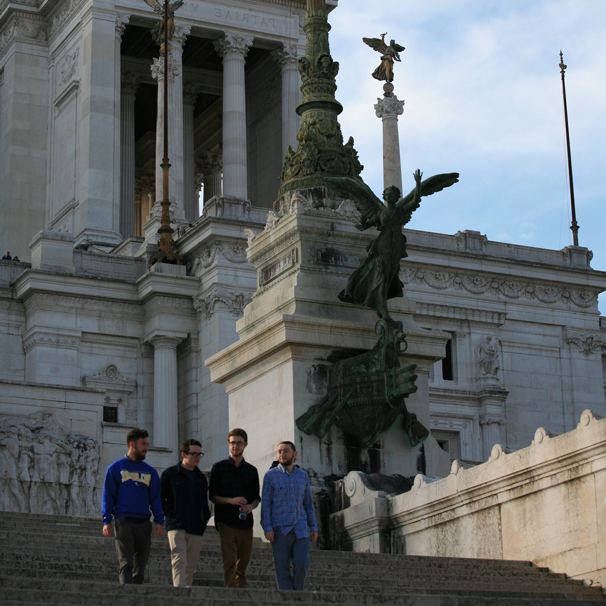 Four students walk down a set of Roman stairs
