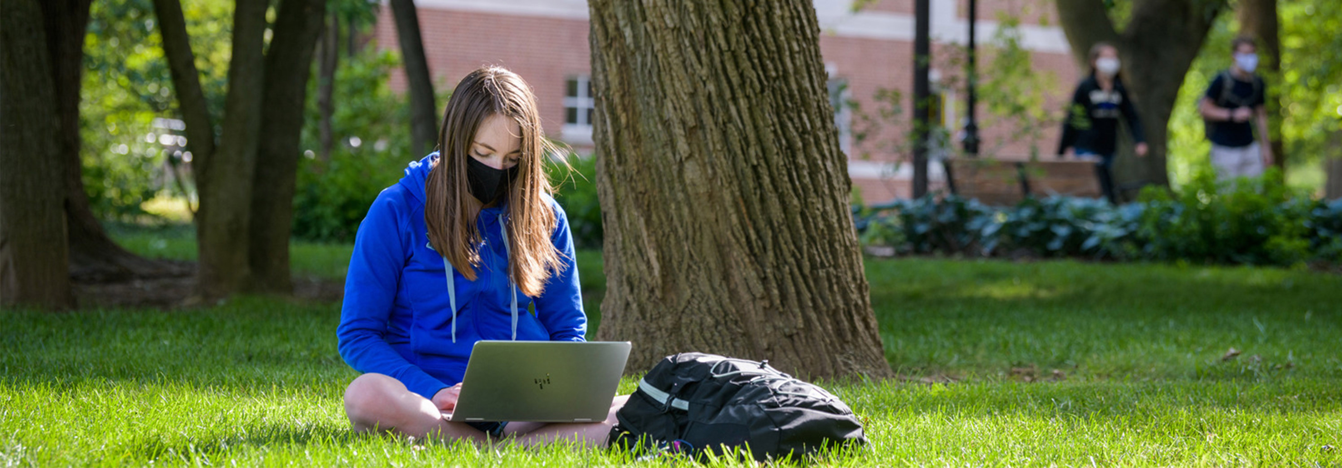 Student in a black cloth mask wearing a blue hoodie sits on the Green while typing a laptop.